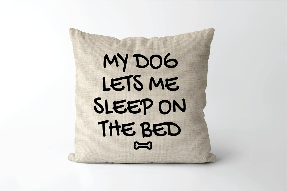 """The pillow cover that says, """"My Dog Lets Me Sleep On The Bed"""""""