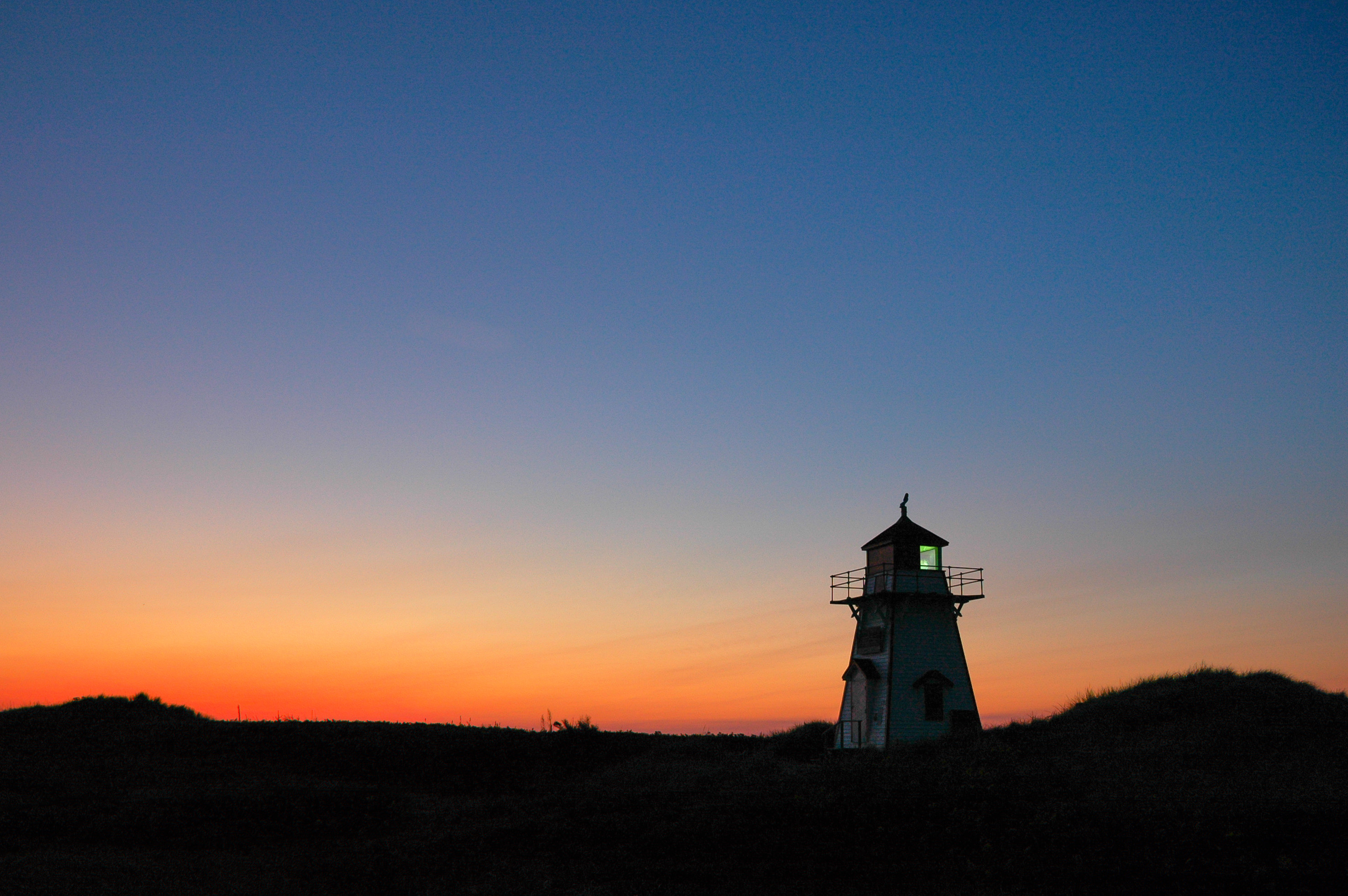 A lighthouse on Prince Edward Island is shown while the sun sets