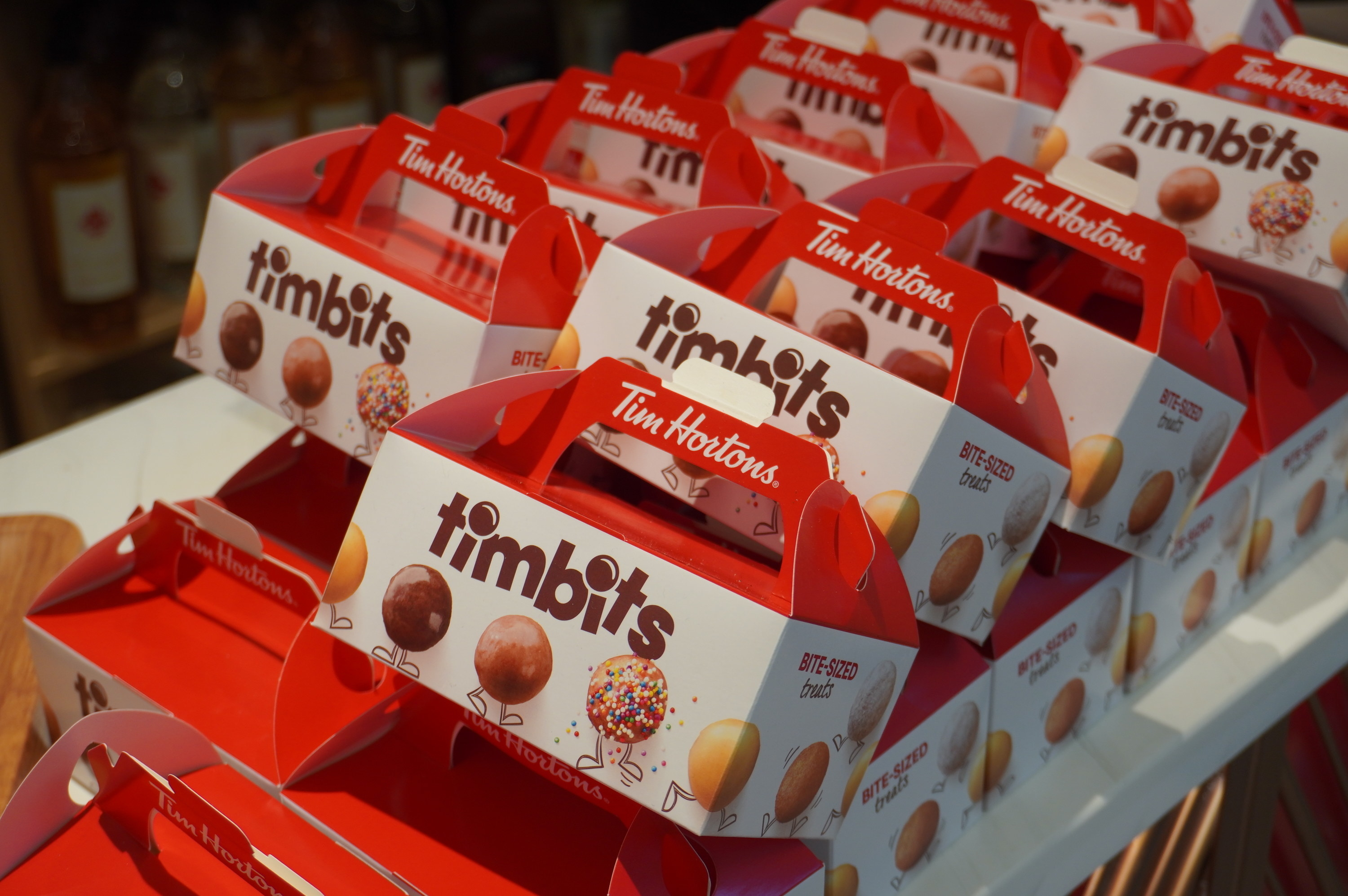 A red and white takeout box of Tim Hortons Timbits are shown with photos of the mini donut holes on the box
