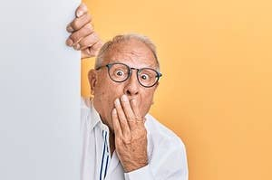A senior man with his hand over his mouth in surprise or embarrassment