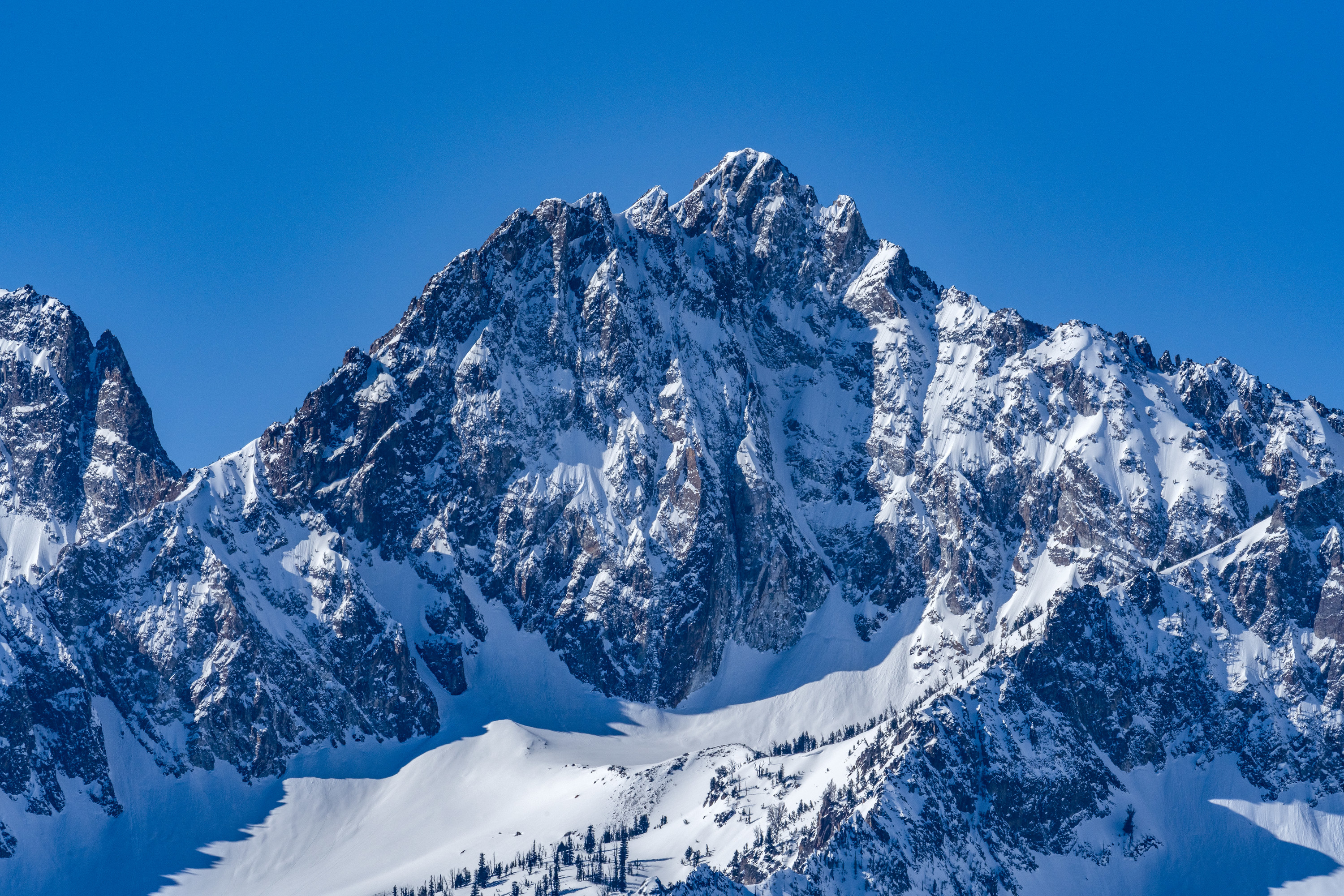 The snowy Rocky Mountains are seen against the backdrop of a clear blue sky
