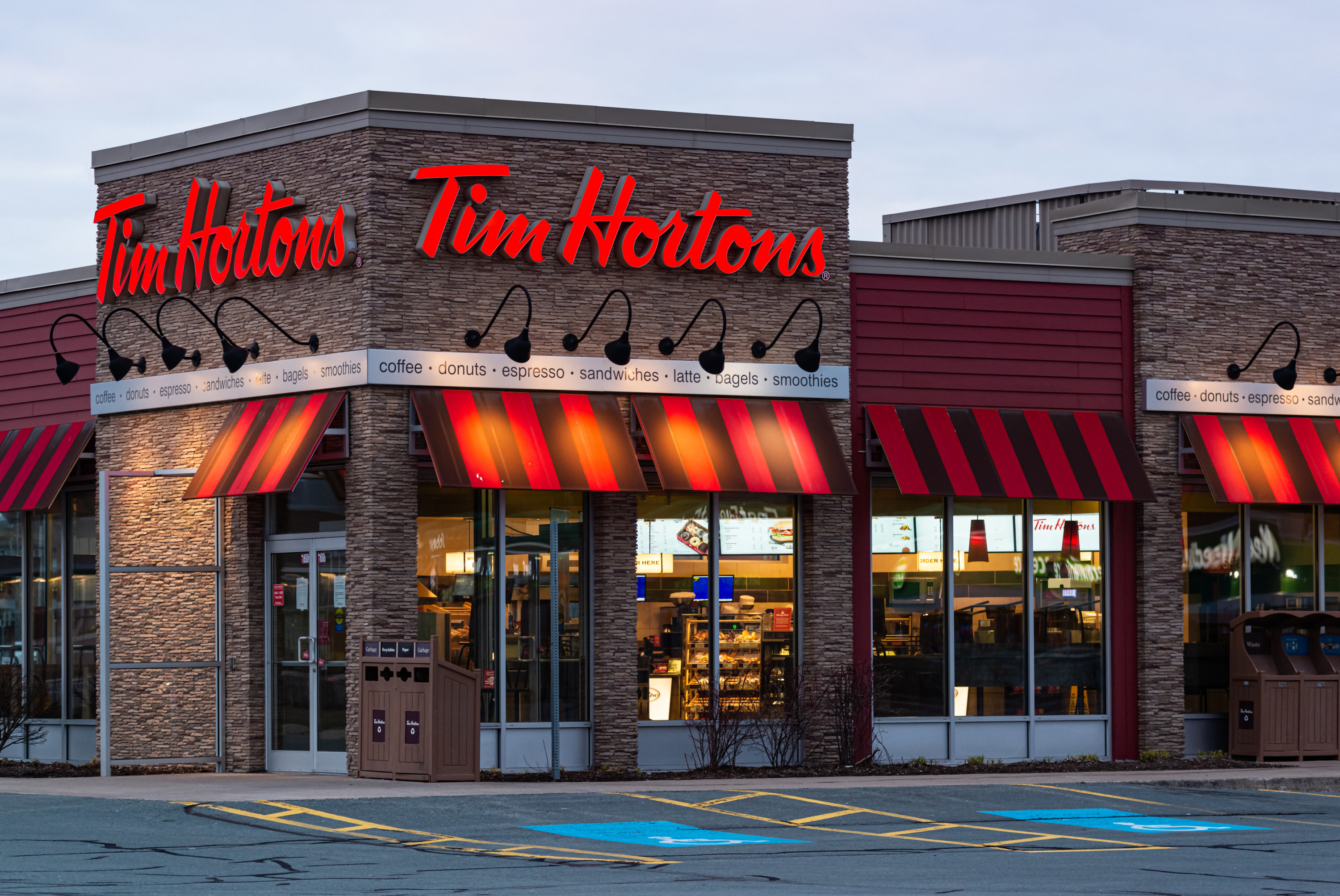"""The restaurant chain Tim Hortons building can be seen with a red and black awning. The words """"Tim Hortons"""" are in red."""