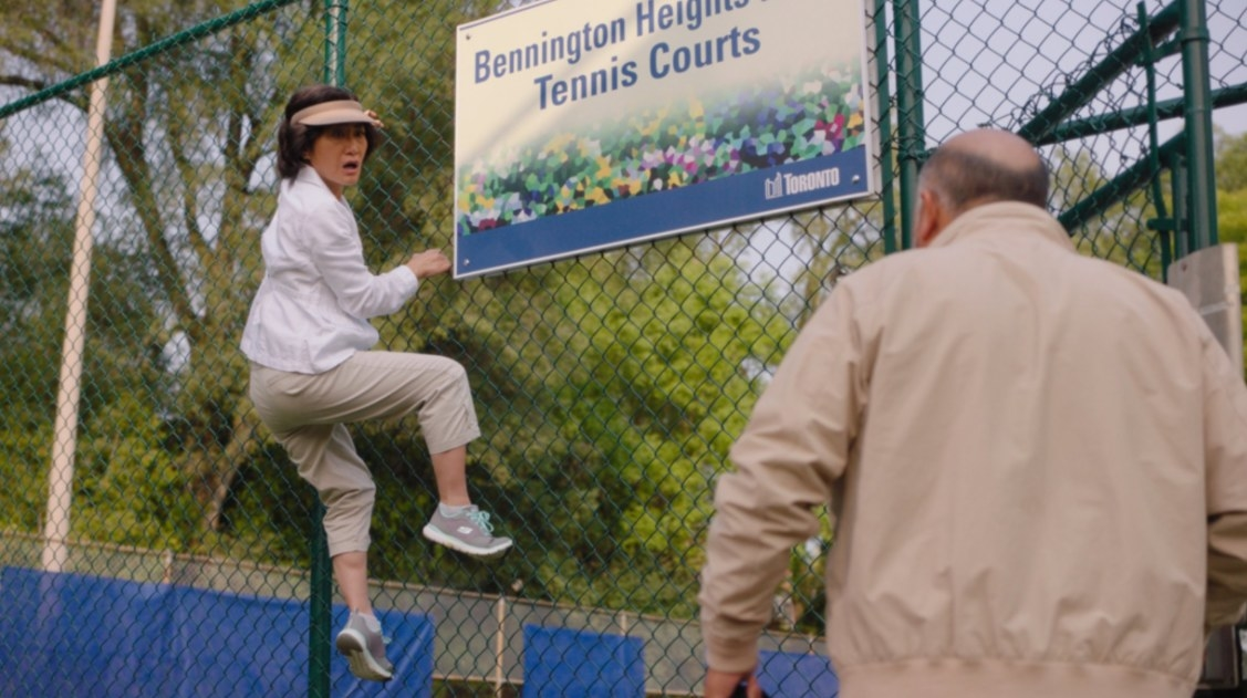 Umma, wearing a visor and tennis clothes, is climbing the chain-link fence of the tennis Bennington Heights Tennis Court.