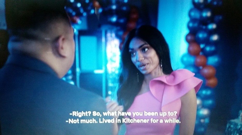 Ingrid wearing a pink one shouldered ruffled dress is talking to Kimchee at their high school reunion