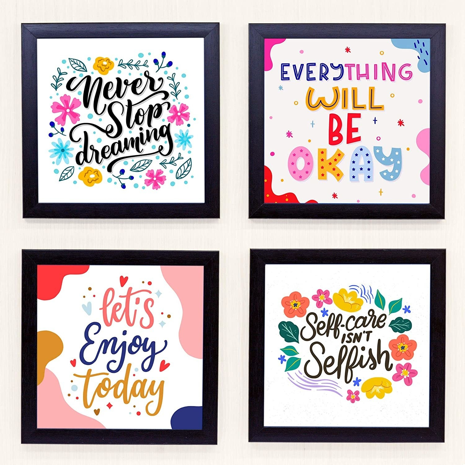 """4 colourful wall frames with quotes like, """"Never Stop Dreaming"""" and """"Self-care isn't selfish""""."""