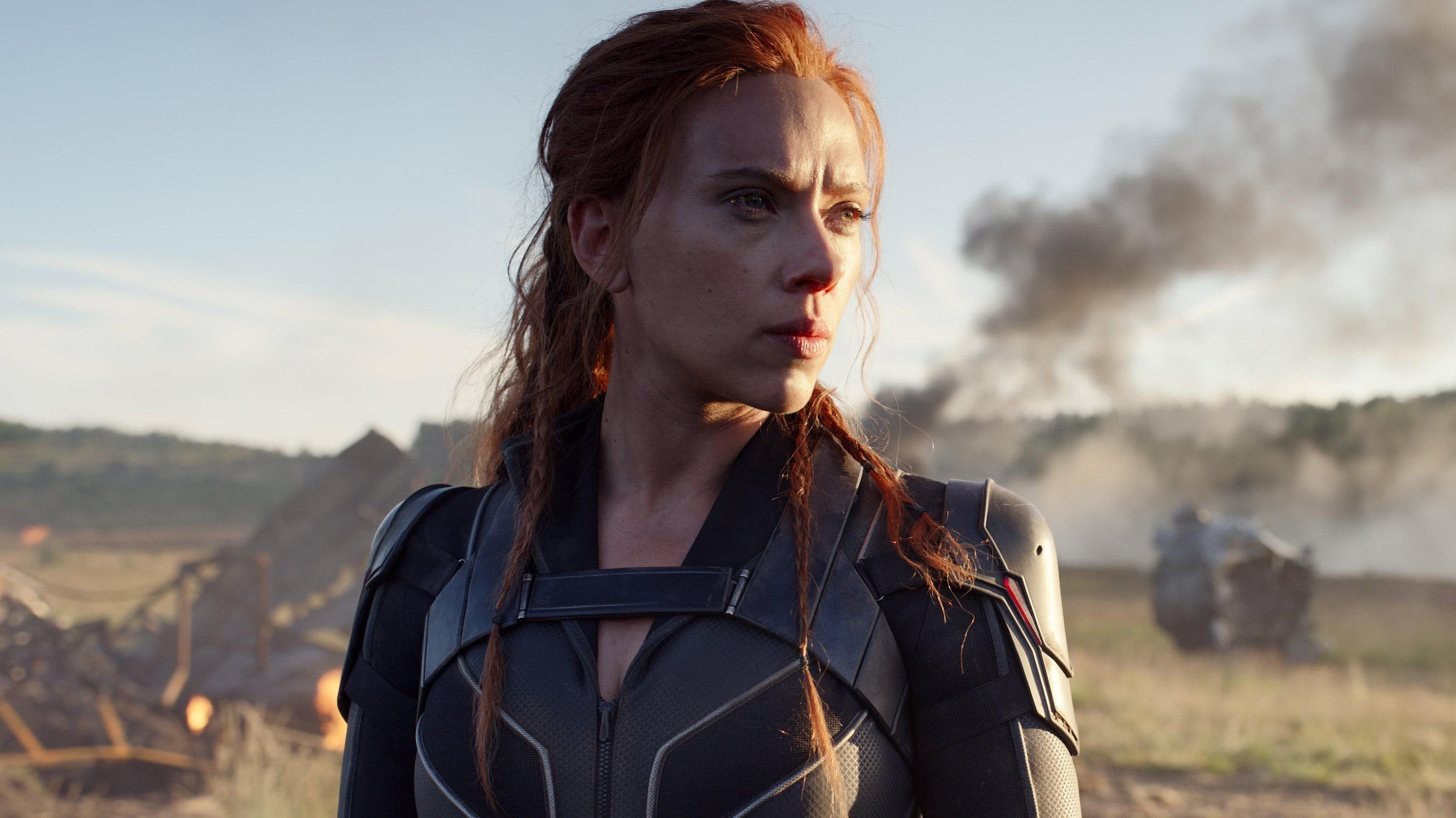 Black Widow looks into the distance in front of a fiery scene