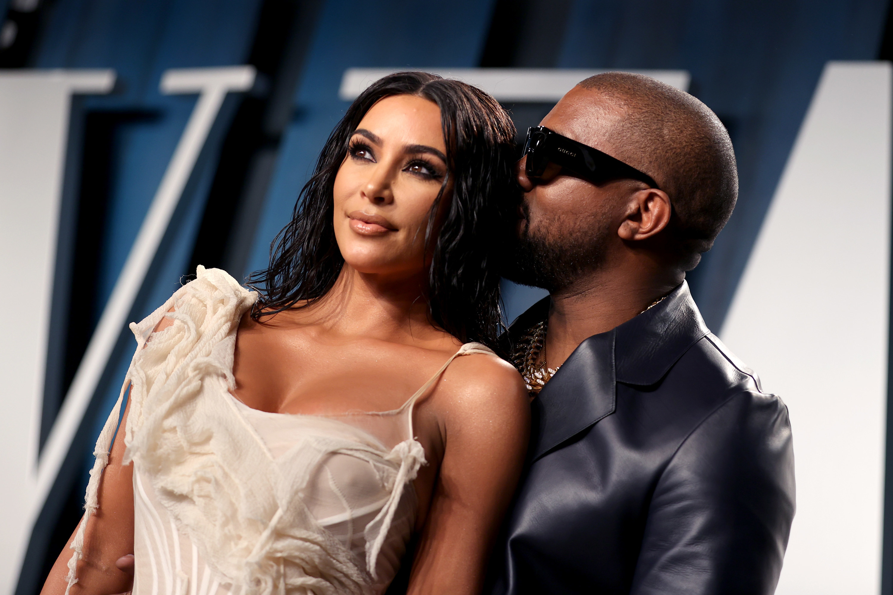 Kim, in a white dress, stands in front of Kanye, in a leather suit