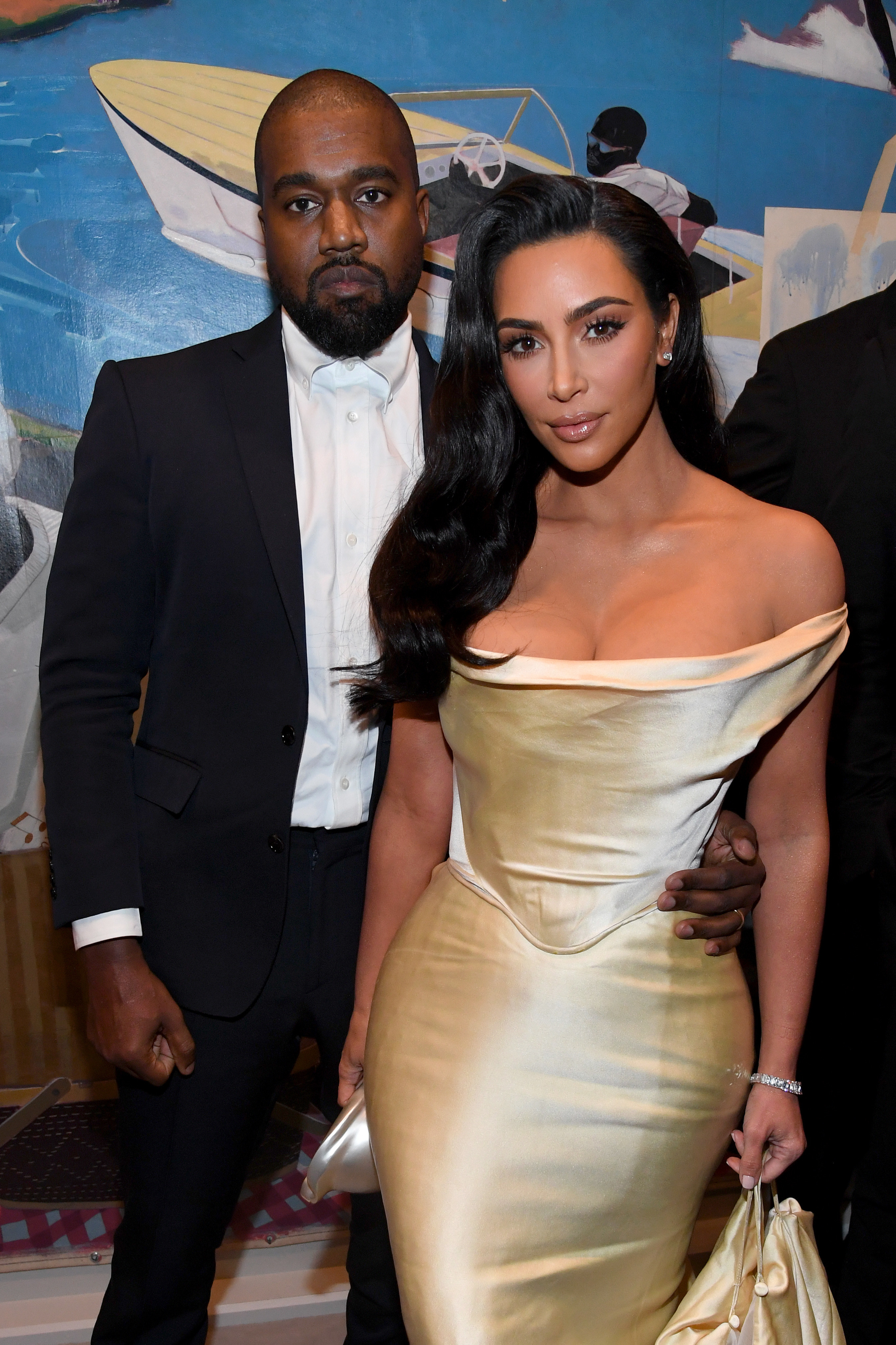 Kanye, in a black suit and white shirt, stands next to Kim, in a gold dress