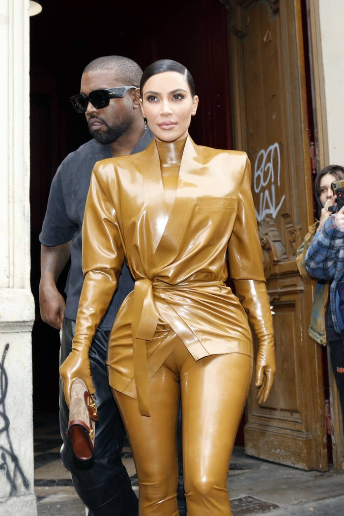 Kim Kardashian, in a yellow leather suit, walks in front of Kanye West, in a black t-shirt and leather pants