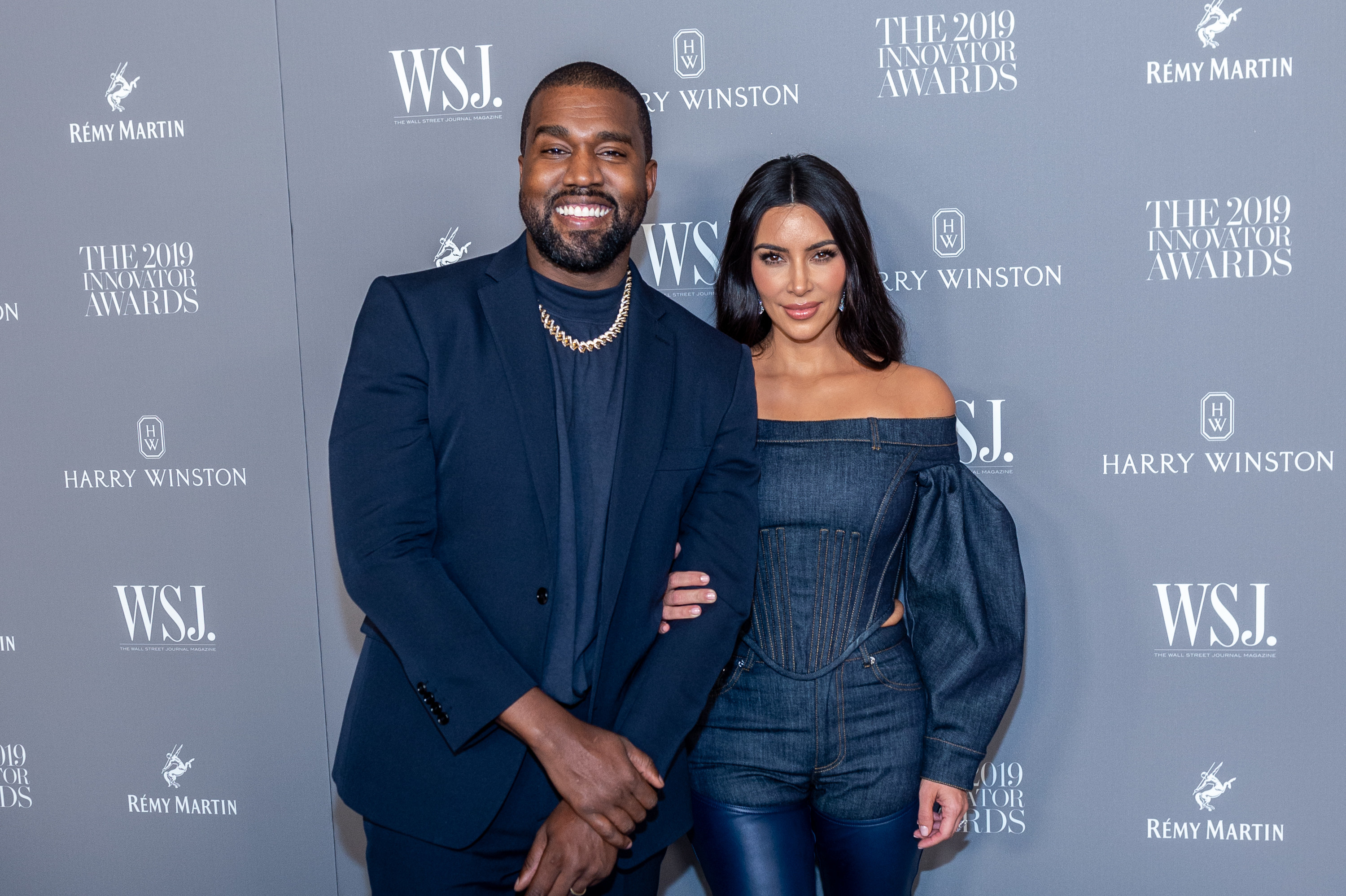 Kanye, in a blue jacket and gold chain and blue shirt, stands next to Kim, in a blue dress