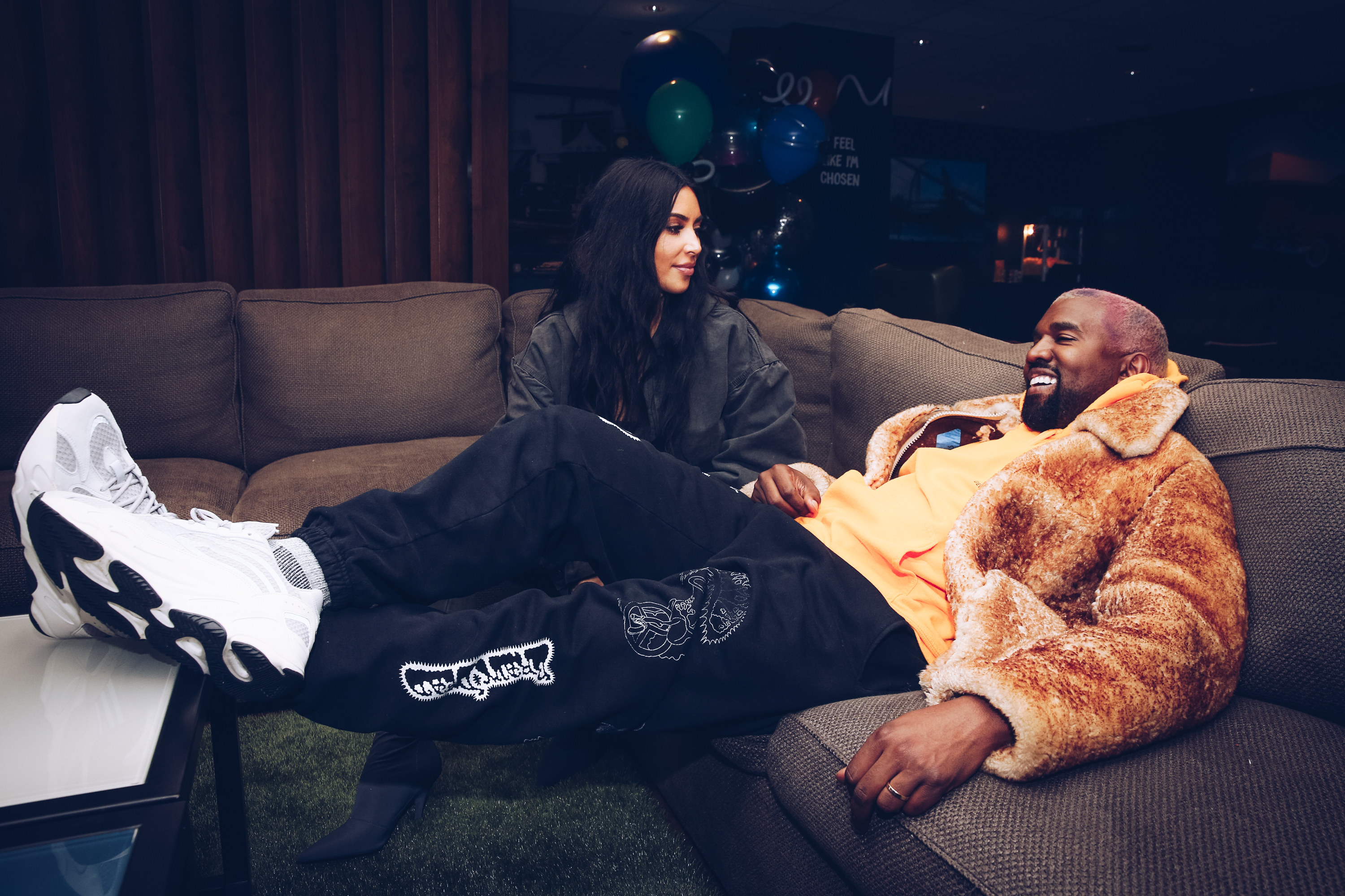 Kim sits next to Kanye on a wraparound couch as he puts his feet up on a table