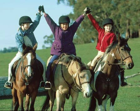 Lara Jean Marshall, Sophie Bennett and Keenan MacWilliam in The Saddle Club riding horses and holding hands