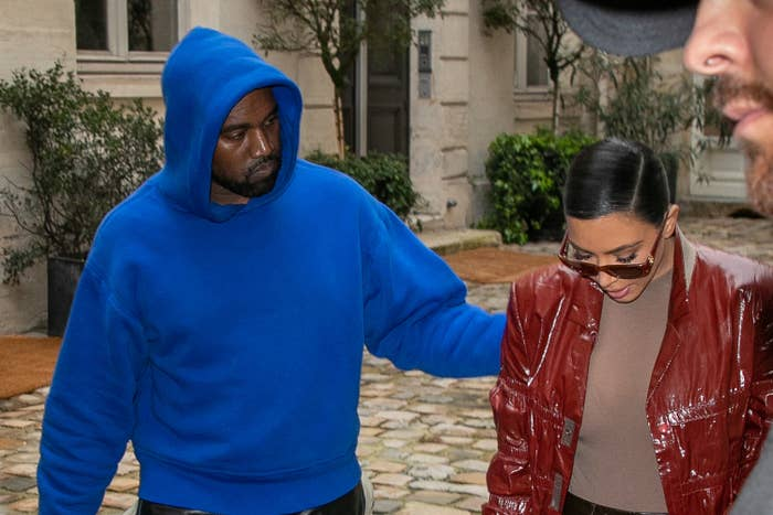 Kanye, in a blue hoodie, puts his arm around Kim, in a red jacket and beige shirt
