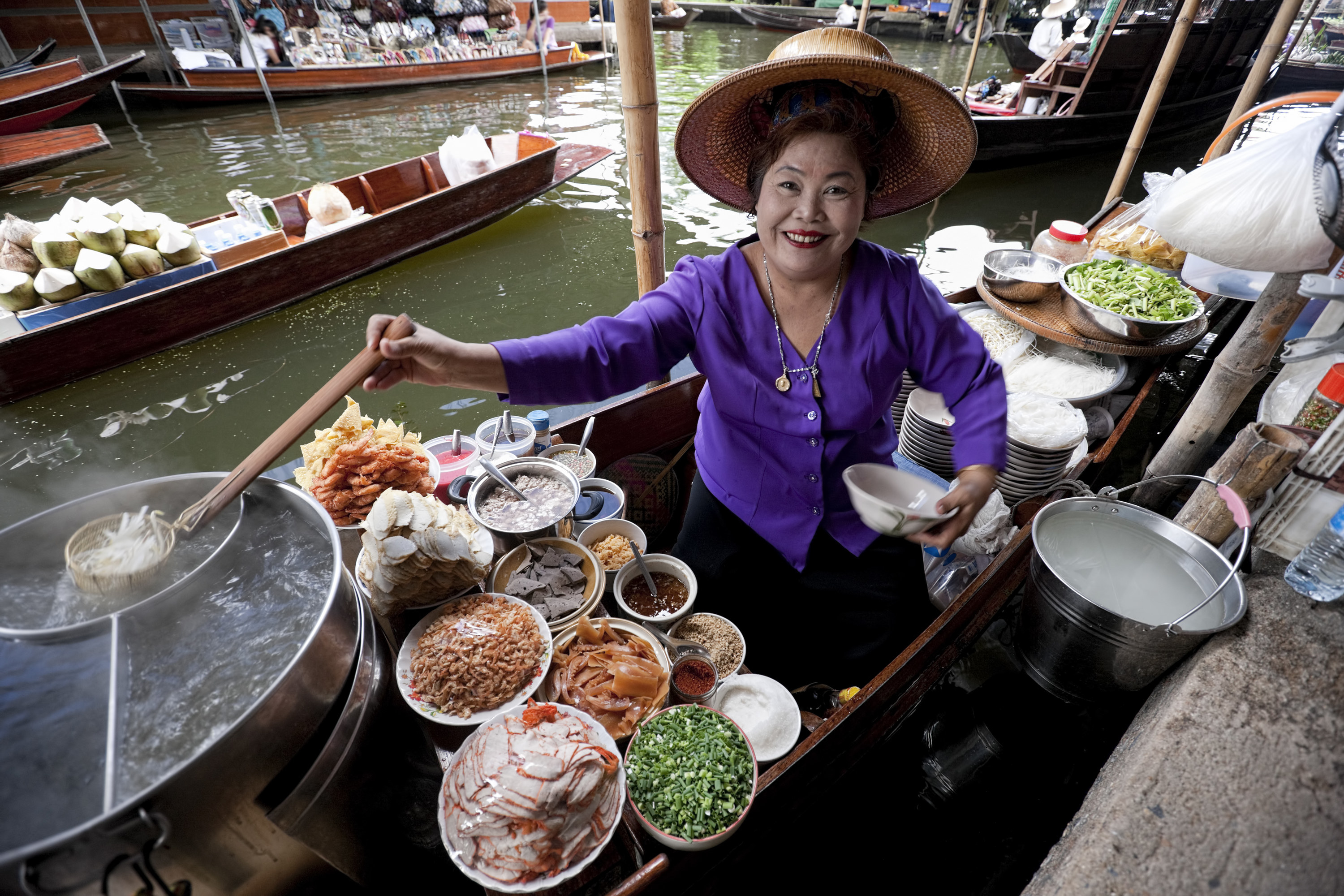 A street foot-vending woman smiles broadly at the camera. She is surrounded by various ingredients and holds a serving of noodles.