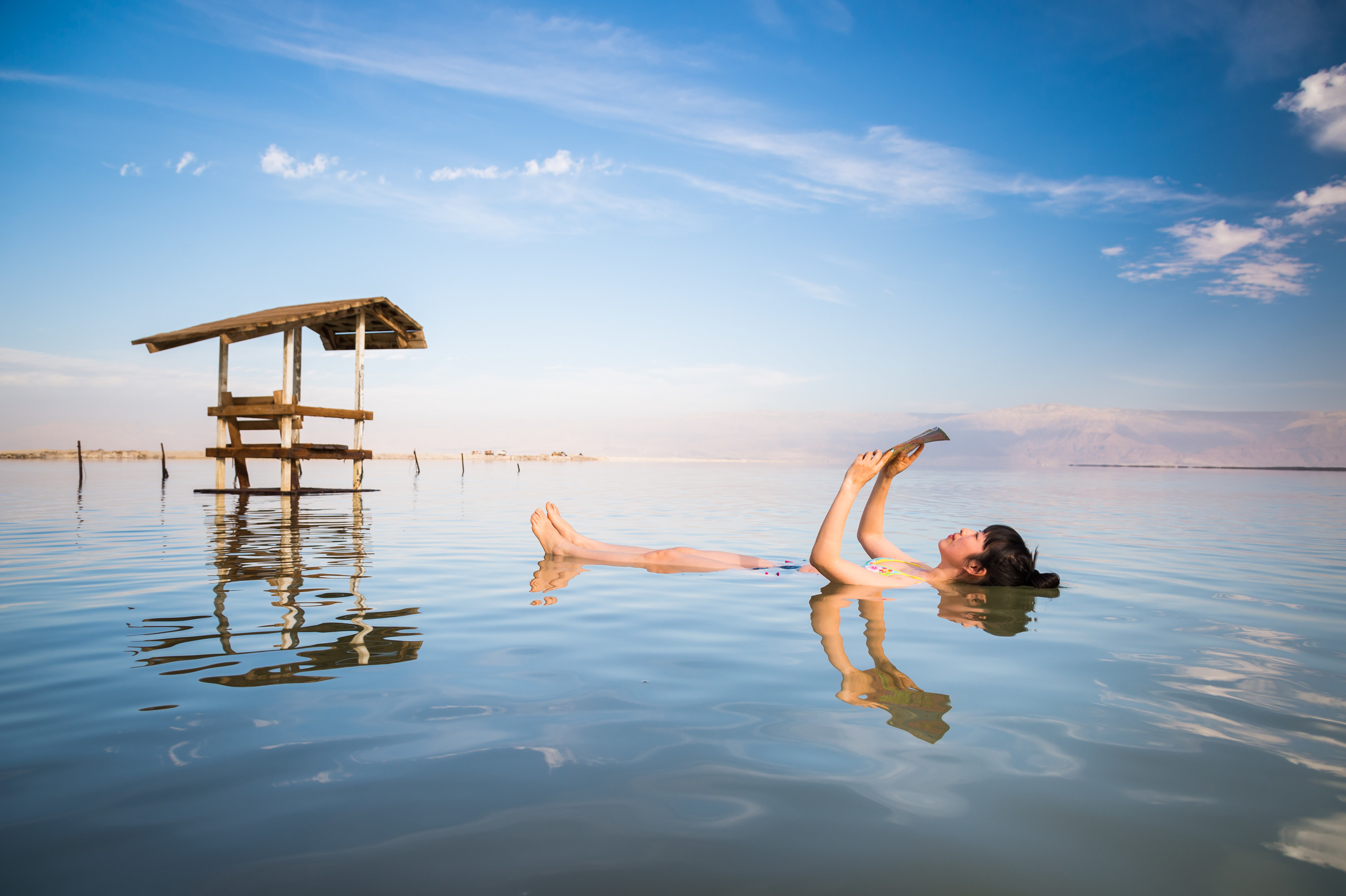 A woman floats along the Dead Sea facing up, and reads a magazine as she floats.