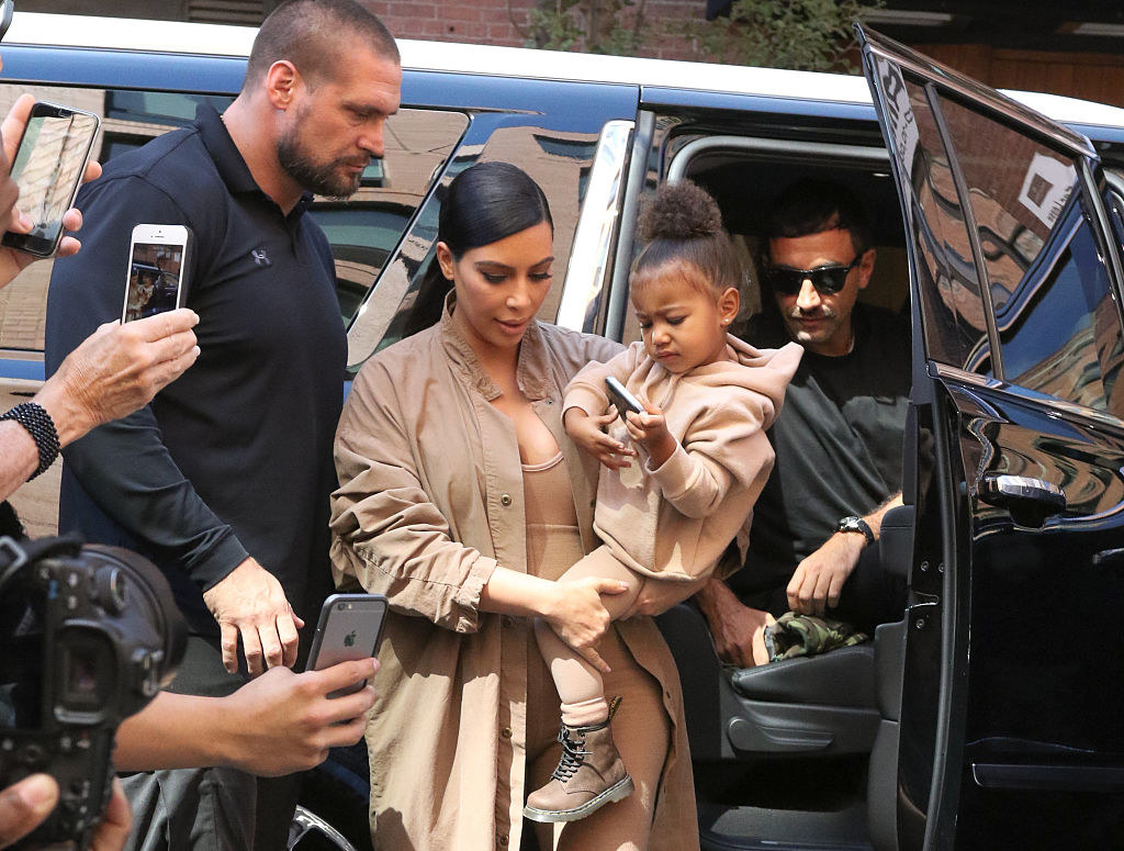 Kim Kardashian is shown getting out of a car, holding her child, as photographers swarm