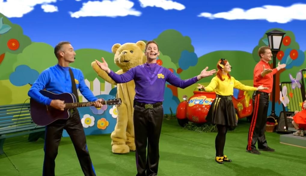 the wiggles and a person in a bear costume dance and sing on a stage