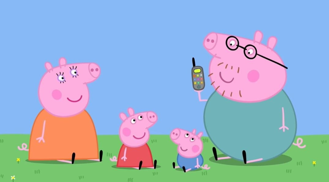 peppa pig's parents and her brother, smiling and sitting in grass