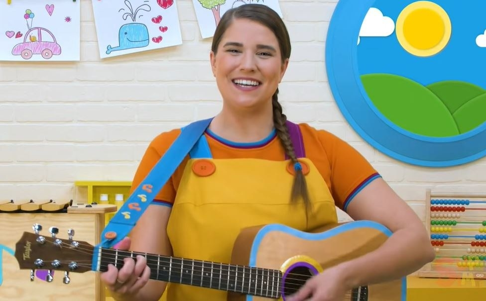 catie (a woman with a long braid) plays an acoustic guitar in a classroom