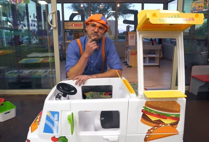 Blippi sits thoughtfully behind a toy food truck