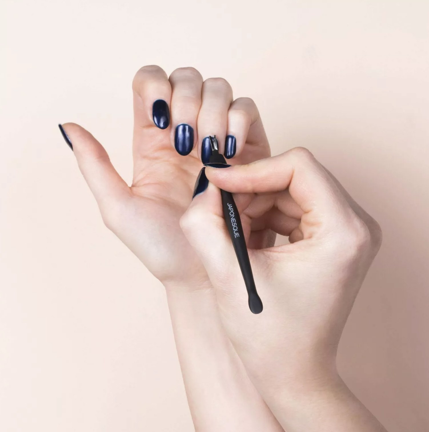 model using the cuticle remover on painted nails