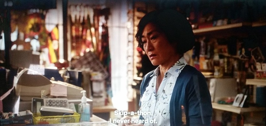 Umma, wearing a dark blue cardigan and a white blouse with flowers, doubts the validity of a customer's claim that her daughter raised money for a Heart & Stroke Skip-a-thon