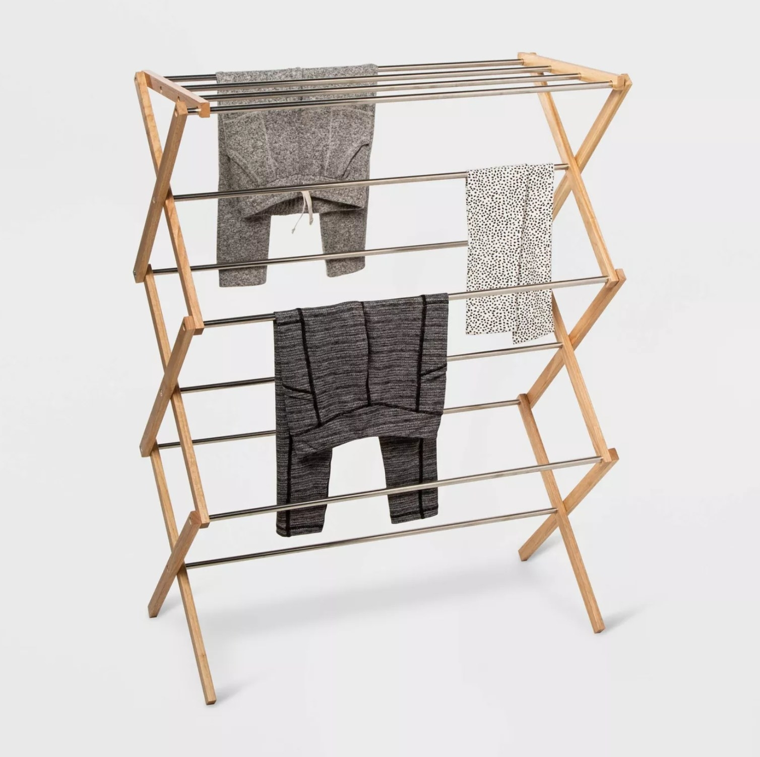 the drying rack with clothes hangin off it