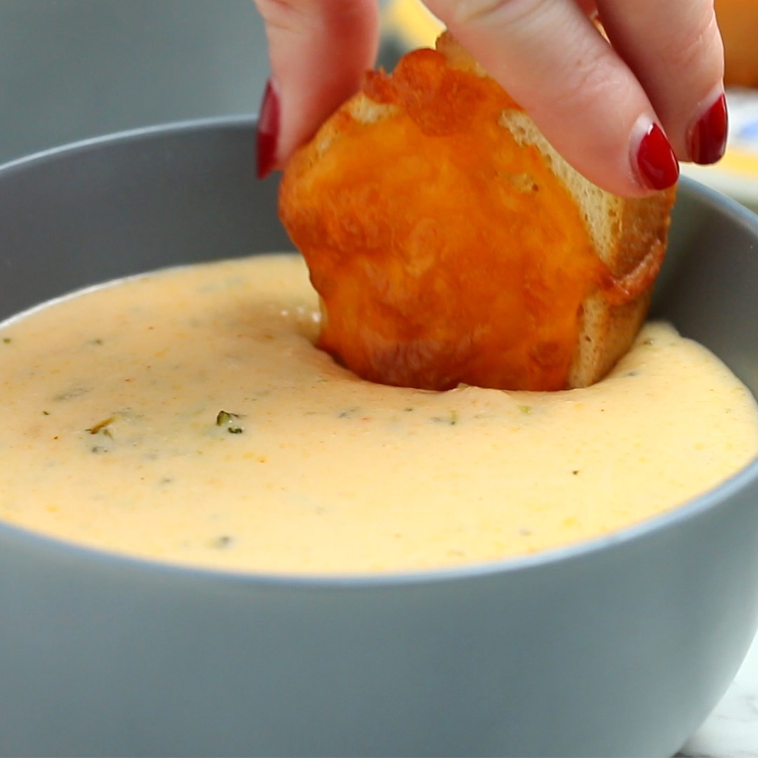 Person dipping bread into a bowl of soup
