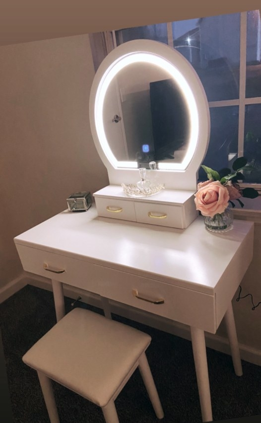 The white and gold vanity with mirror lit up