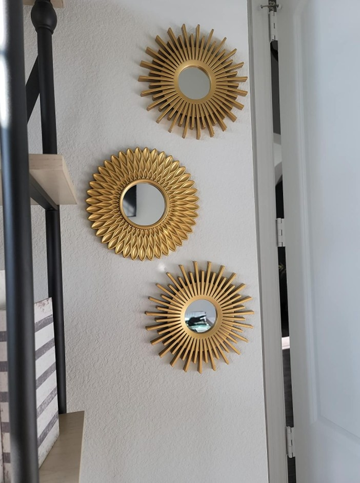The three gold round mirrors on a reviewer's wall