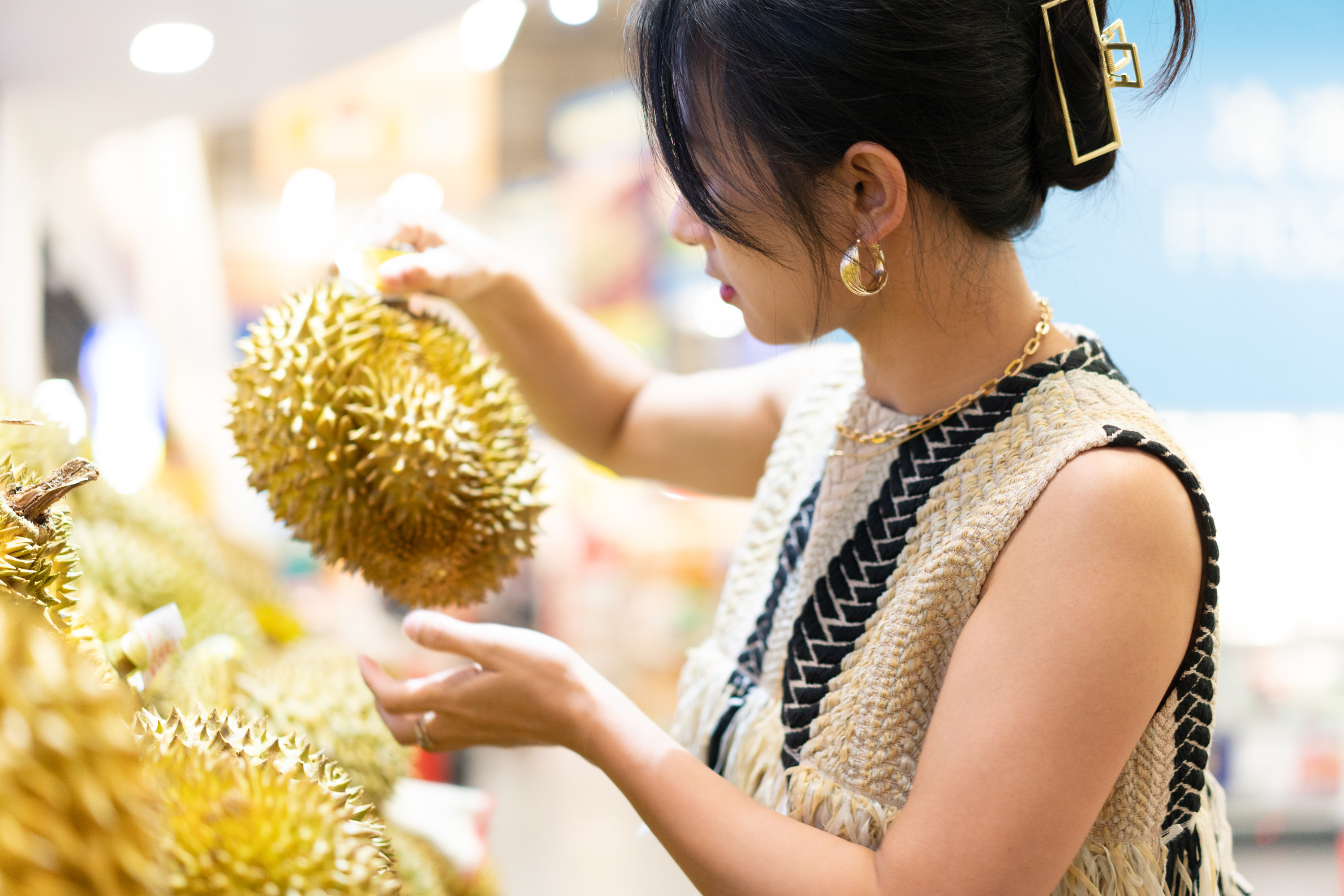 A woman holds up a durian