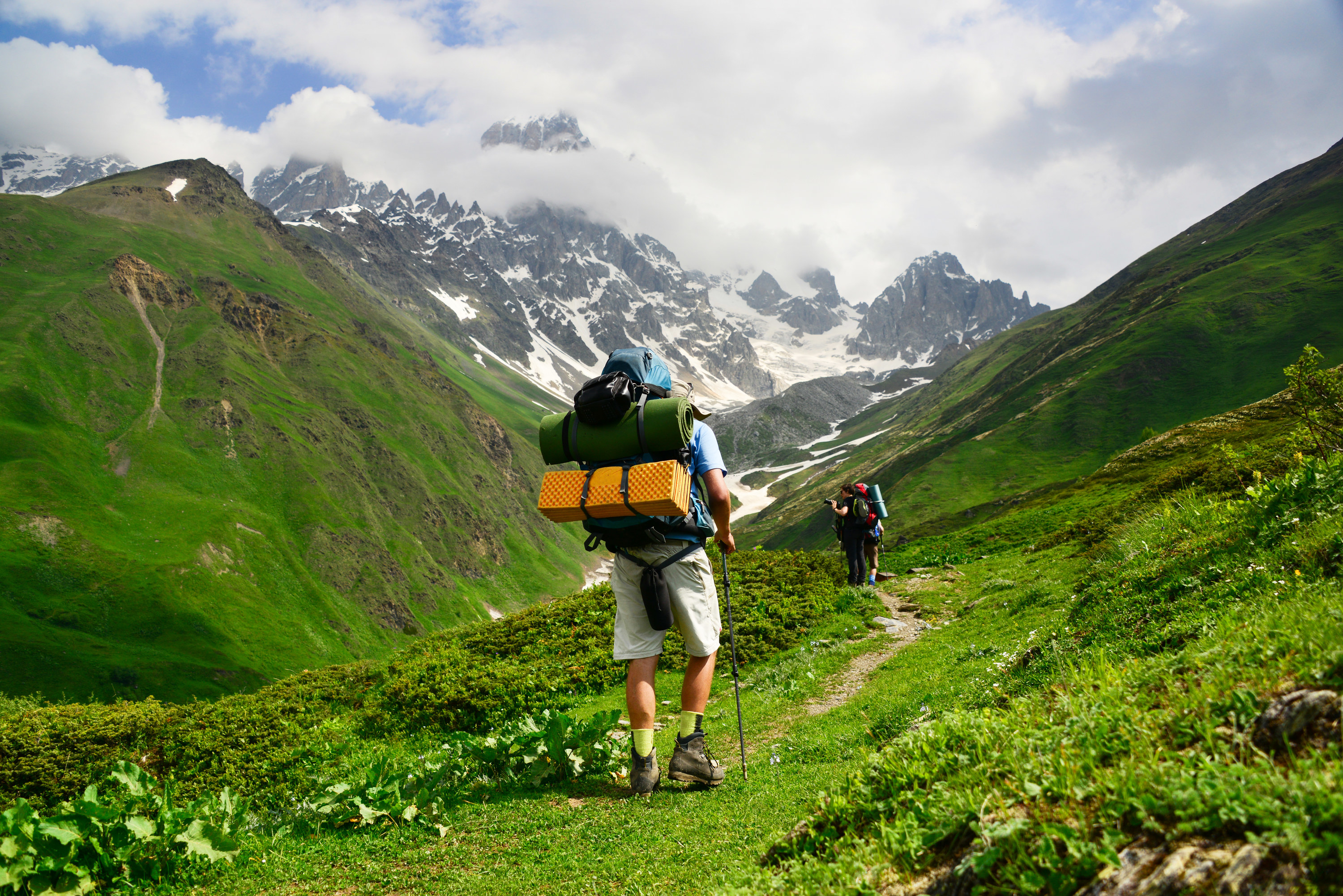 Man with hiking backpack climbs the mountains of Tbilisi.