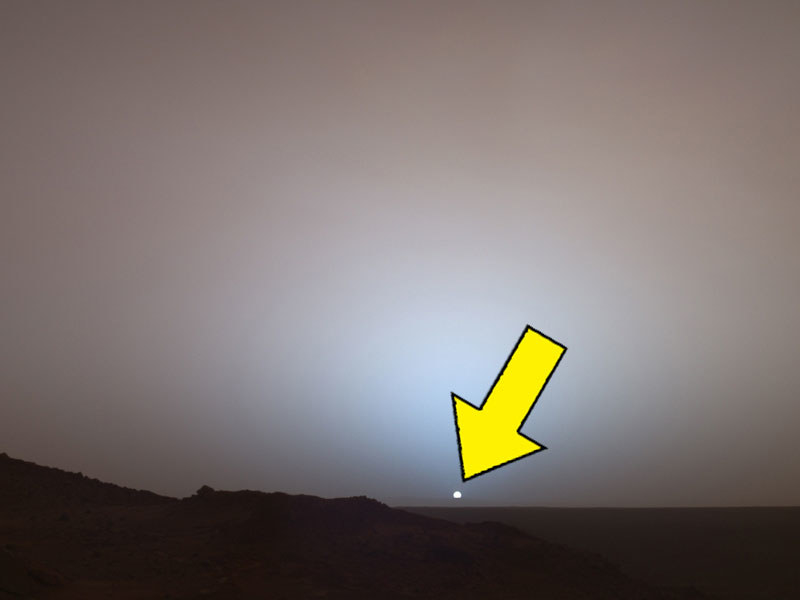 A small dot in the sky over Mars slinking behind a darkened landscape