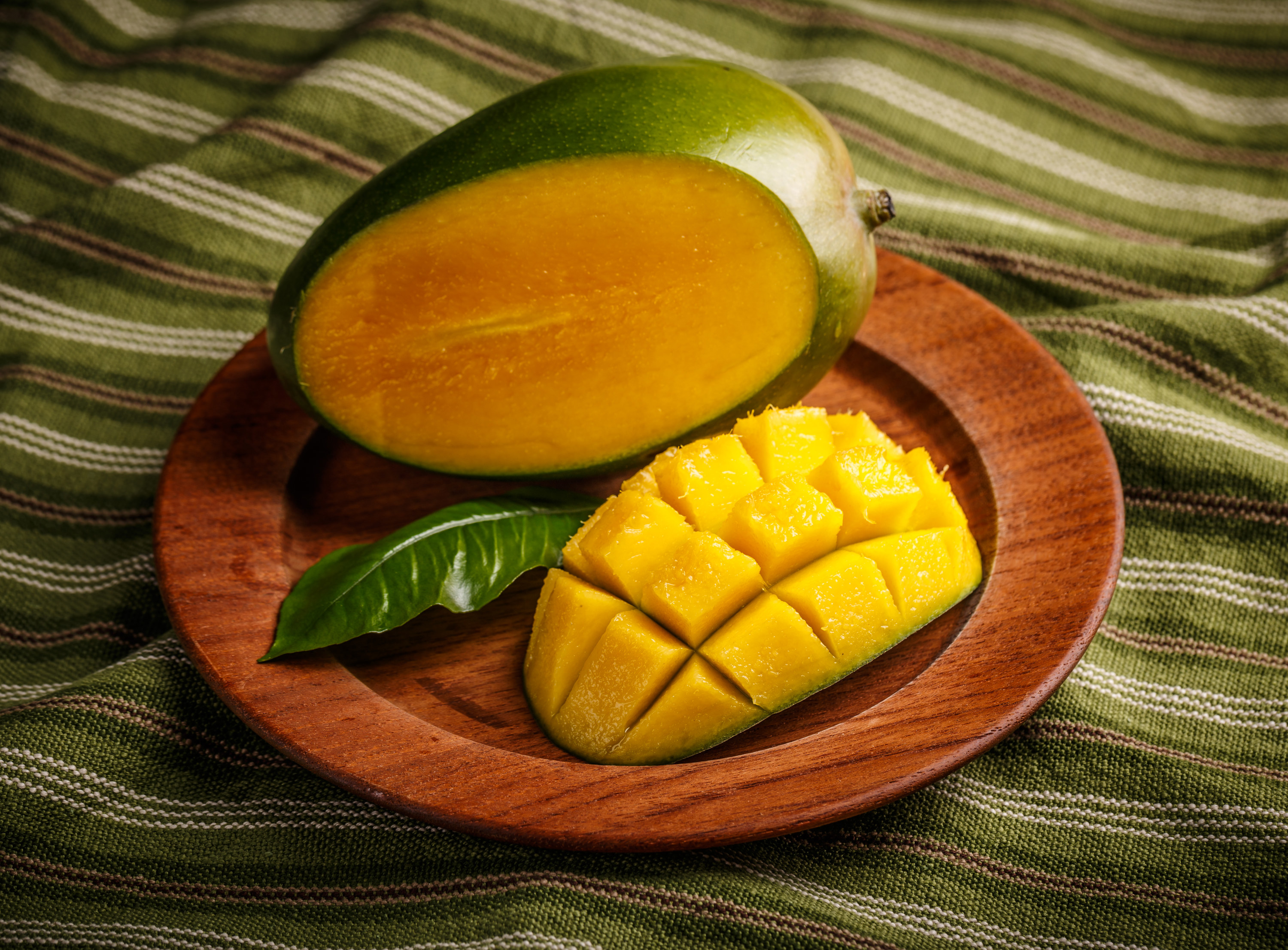 A mango and a green leaf are on a wooden plate. The mango has been sliced open with part of it cut into cubes. Underneath the wooden plate is a green towel with thin dark-green, white, and reddish-brown stripes