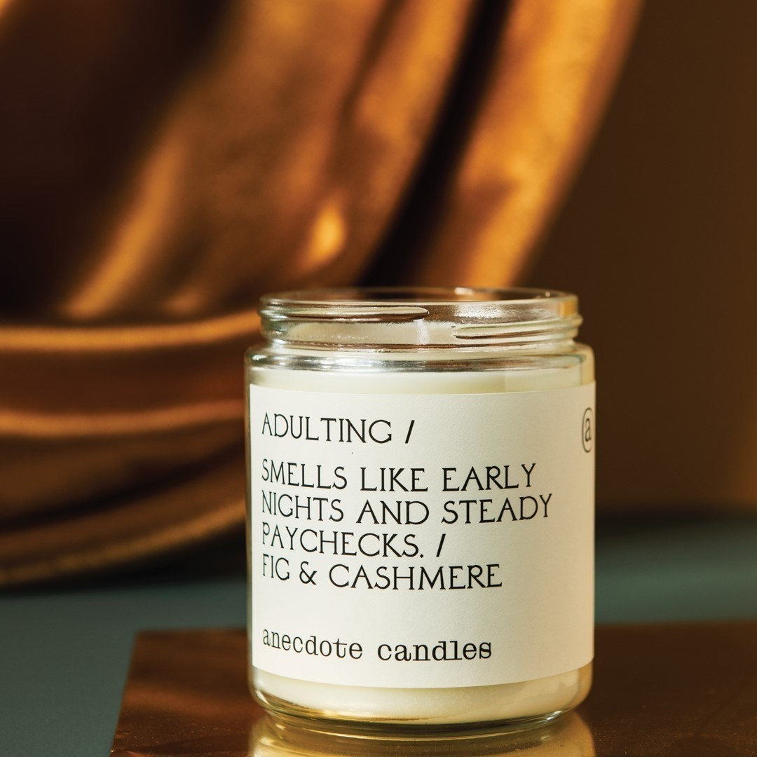 A candle with a label that says smells like early nights and steady paychecks