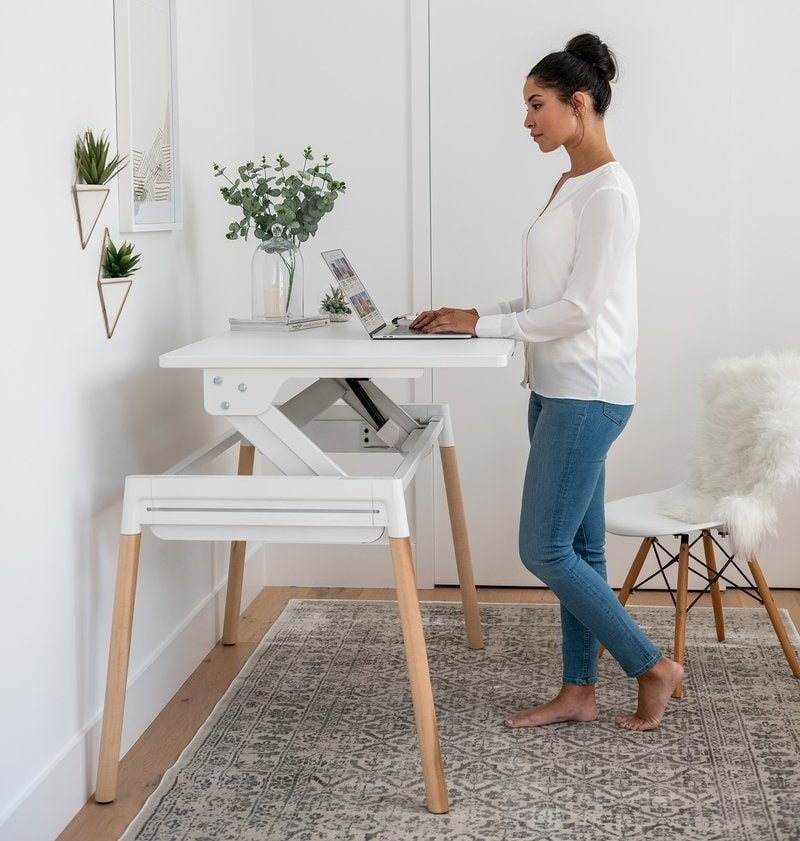 A person standing at a desk working on their laptop