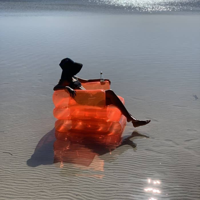 A person sitting on a large inflatable beach chair on the sand