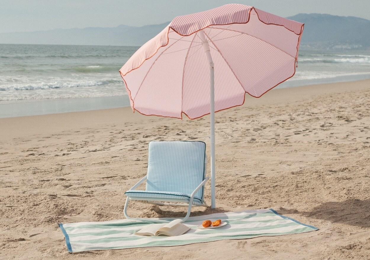 A large beach umbrella with and a towel in the sand