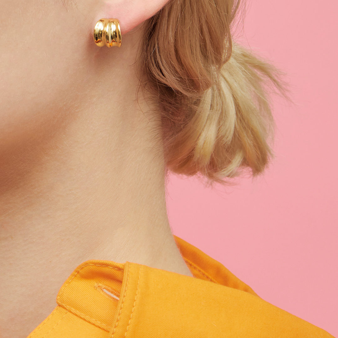 A close up image of someone wearing a small hoop earring in their ear