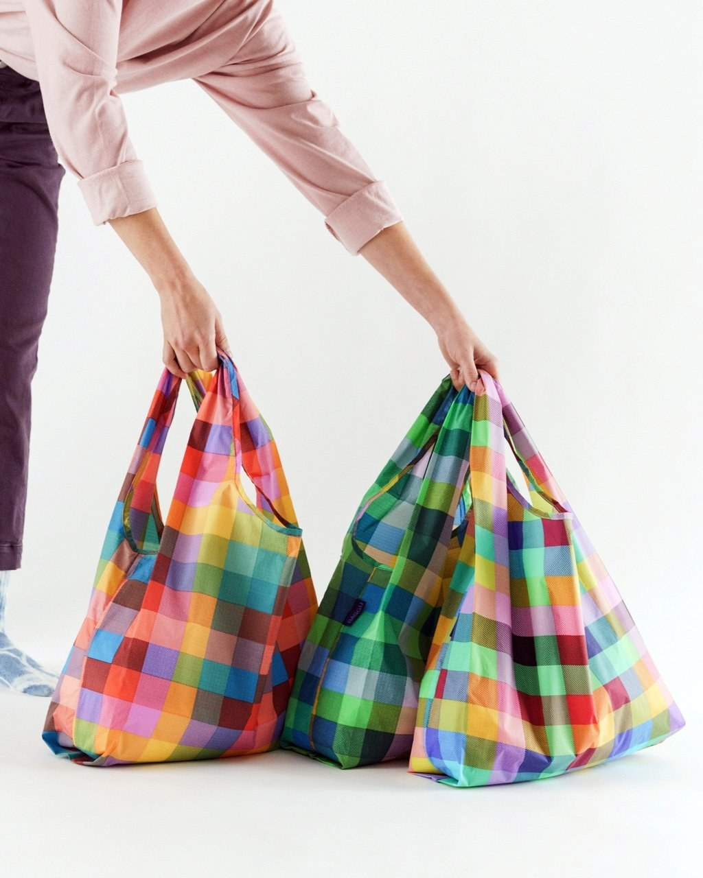 A person holding a bunch of full shopping bags