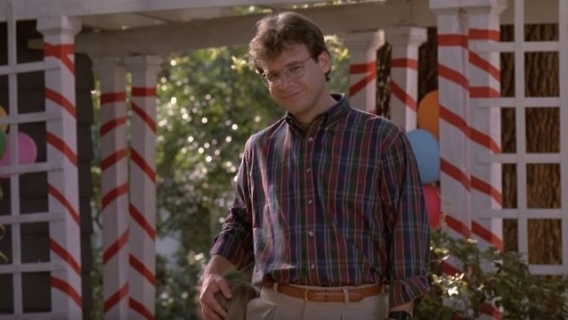 rick moranis in plaid shirt and khakis smiles slightly