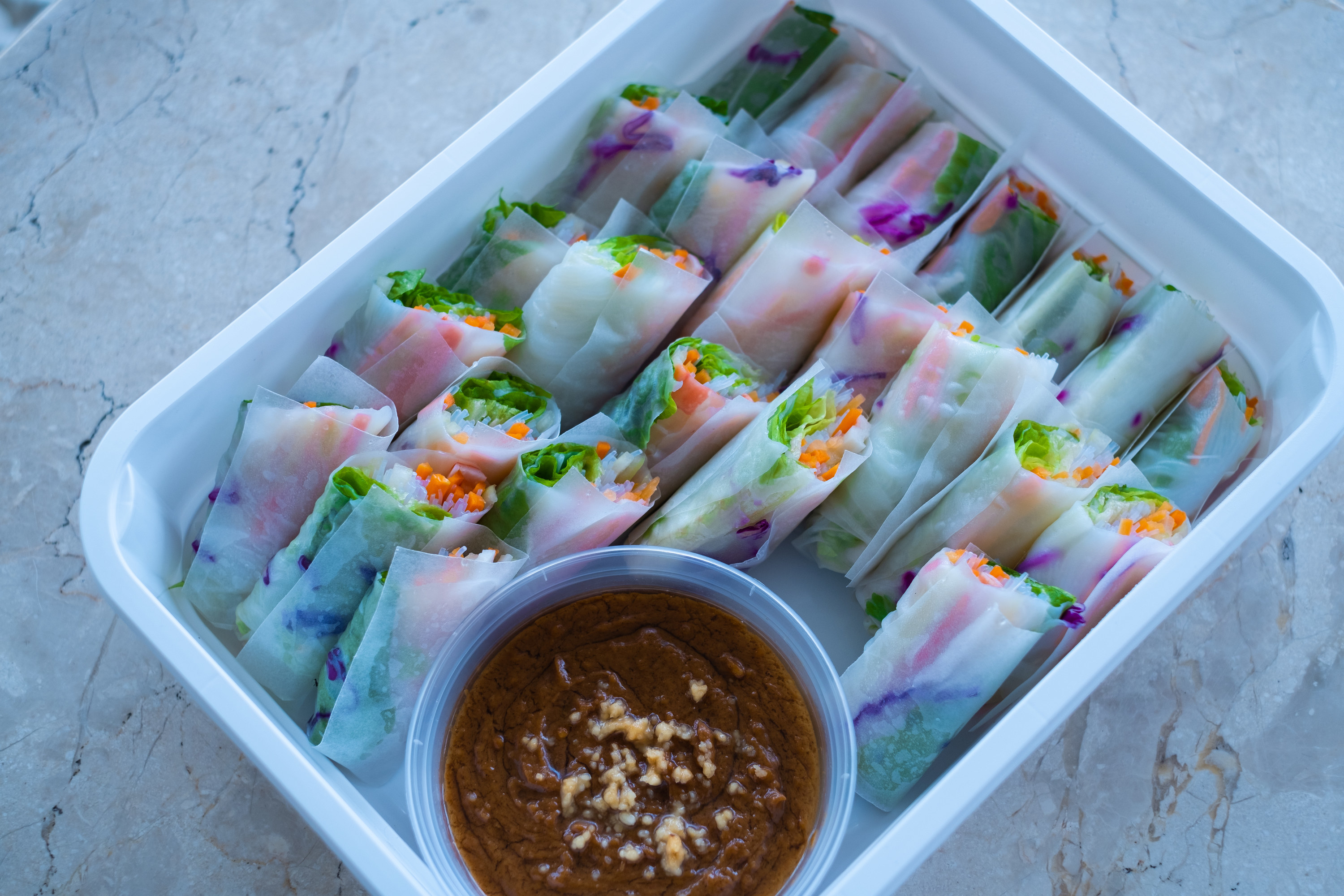 Twenty-five spring rolls and accompanying dip are in a white rectangular container