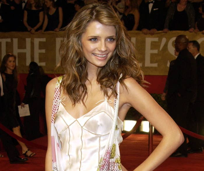 Mischa puts her hand on her hip while posing on a red carpet