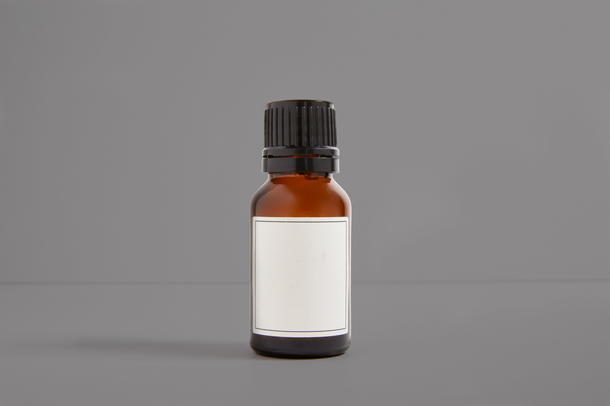 Small brown bottle with black plastic screw on top with white label sits alone on a gray field