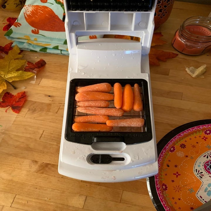 Reviewer's photo of baby carrots in the veggie slicer, open