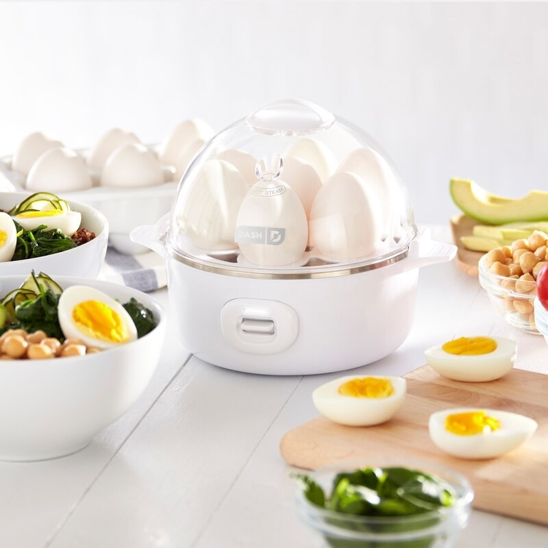 An egg cooker on a table surrounded by perfectly cooked eggs