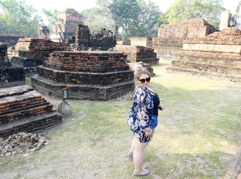 plus size reviewer at a tourist site of ruins wearing shorts
