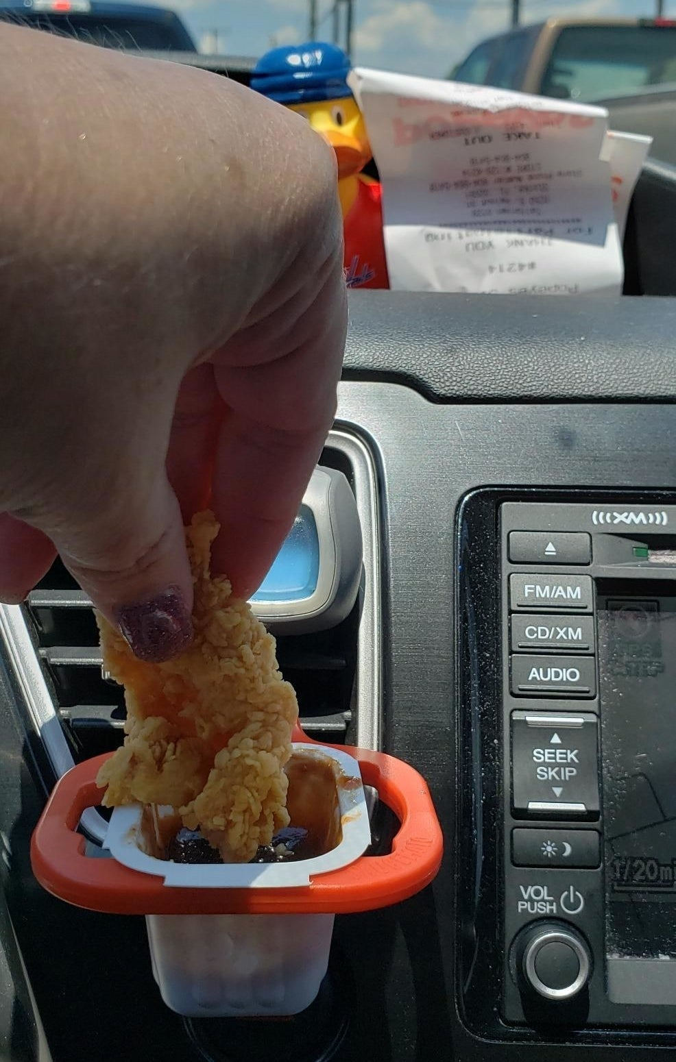 reviewer dunking a chicken tender in a sauce packet that is attached to a sauce holder