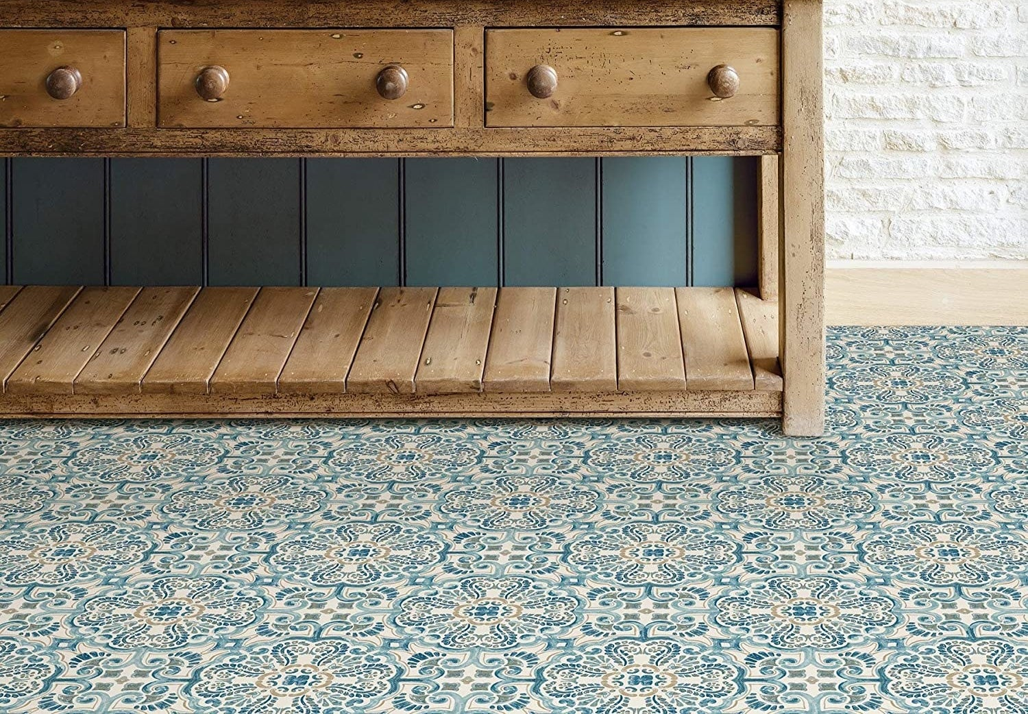 A wooden credenza on a funky patterned tiled floor