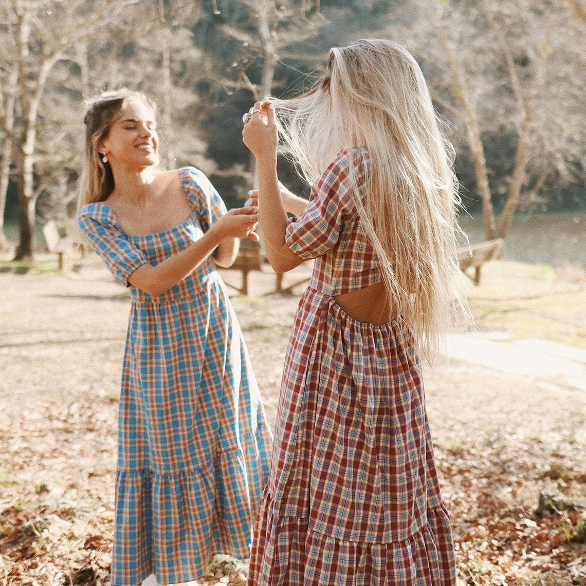 Two models laughing while wearing the gingham midi dress in blue (right) and red (left)